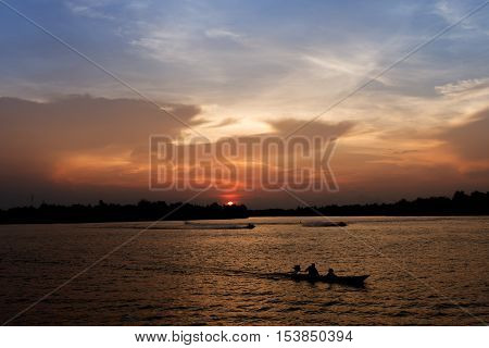 Silhouette of long tail boat on Tapee river Suratthani Thailand in evening time