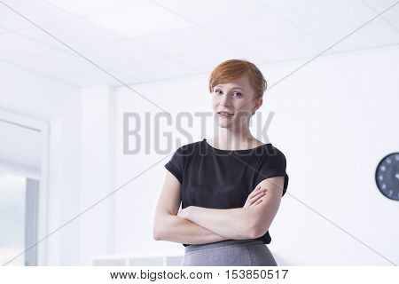 Young red haired woman standing in the bright interior with her arms folded