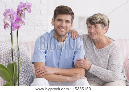 Senior woman sitting on a couch with her young and smiled caregiver