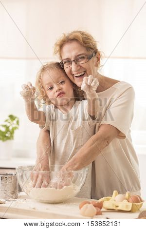 Senior Nanny Standing Behing Child During Cooking