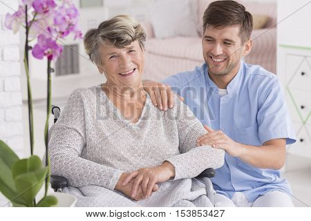 Smiling Nurse Sitting Close To The Woman On Wheelchair