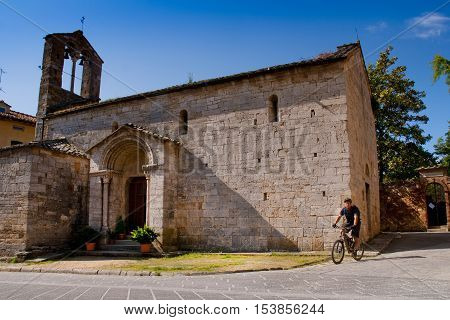 Val d'Orcia Siena mountain bike excursion in the Tuscan hills - passage from the Collegiate Church San Quirico d'Orcia