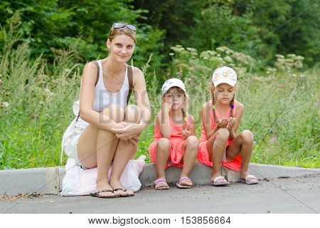 Mother And Two Children Sitting On The Curb Of The Road Waiting For The Bus