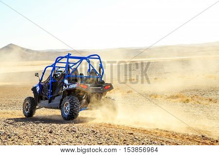 Merzouga Morocco - Feb 25 2016: Back view on blue Polaris RZR 800 with it's pilot in Morocco desert near Merzouga. Merzouga is famous for its dunes the highest in Morocco.