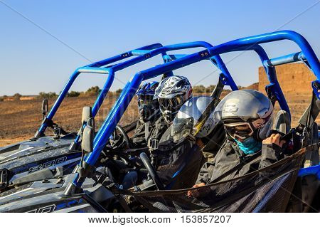 Merzouga Morocco - Feb 25 2016: Side view on blue Polaris RZR 800 with it's pilot and passengers in Morocco desert near Merzouga. Merzouga is famous for its dunes the highest in Morocco.