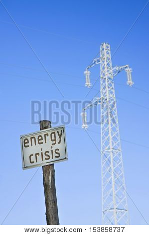 Energy Crisis written on road sign near electricity pole