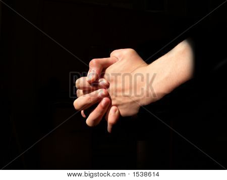Two hands clenched in a tight prayer in a the light. poster