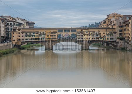 FLORENCE ITALY- OCTOBER 23 2016: View of medieval stone bridge Ponte Vecchio and the Arno River from the Ponte Santa Trinita (Holy Trinity Bridge) in Florence Tuscany Italy. Florence is a popular tourist destination of Europe