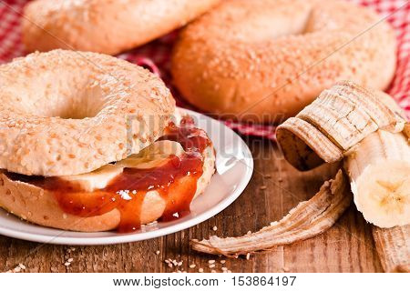 Sesame bagels with jam and banana on white dish.