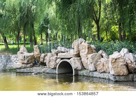 Dam with drain pipe located in the public garden. Dam decor consist from flowers and boulders.