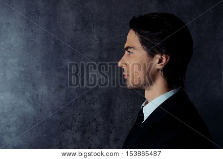 Side-view photo of harsh young man in formalwear