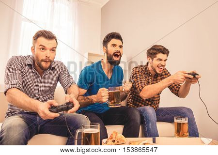 Portrait Of Excited  Cheerful Men Play Video Game With Beer And Pizza