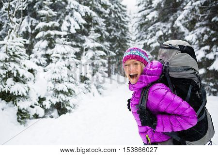 Happy young woman hiking in white winter forest woods with backpack. Girl walking on snowy trail. Inspirational Travel and healthy lifestyle Motivation and. Camping outdoors in winter landscape.