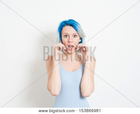 Young beautiful blue hair alternative hipster woman stunned expression looking at camera with hand covering mouth on white background