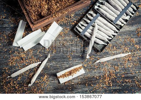 Cigarette cases and handmade cigarettes on old wooden table