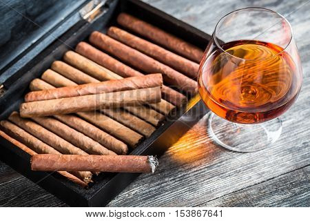 Cigars in humidor and cognac on old wooden table