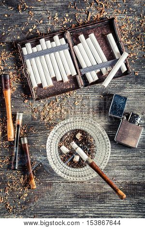 Cigarettes ashtray and a smoking pipe on old wooden table
