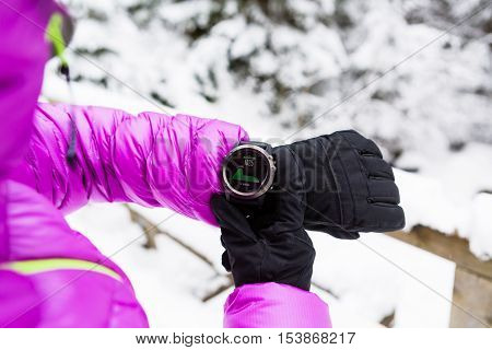 Woman hiker checking the elevation on sports watch smartwatch with altimeter app in winter woods and mountains. Female trekker trekking in white snowy forest with electronics wearable technology.
