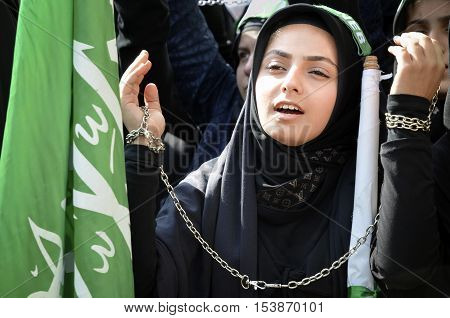 Istanbul Turkey - October 11 2016: Shia Muslim women mourn during Ashura. Shiite Muslim women hold up their chained hands as they mourn during an Ashura procession. Turkish Shia Muslims mourning for Imam Hussain. Caferis take part in a mourning procession