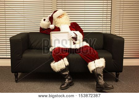 Santa Claus  sitting on sofa in his office holding blank whiteboard with space for copy - lack of motivation