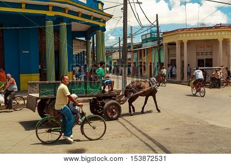 People sitting and riding in horse drawn carriage at the square of Cuban town Moron on bright sunny day