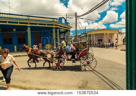 Cayo Coco island, town Moron, Cuba, July 23, 2013, People sitting and riding in horse drawn carriage  at the square of Cuban town Moron on bright sunny day