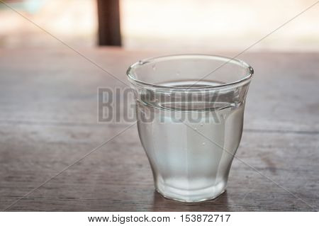Drinking water in a glass on wooden table, stock photo