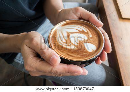 Hand on hot coffee latte stock photo