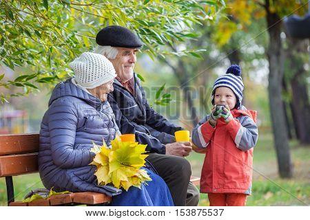 Senior couple and grandson drinking hot tea in autumn park