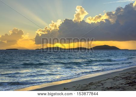 Vivid rays from rising sun shine brilliantly from behind clouds over tropical Caribbean island of Culebrita and reflect on sea and Zoni Beach on Isla Culebra
