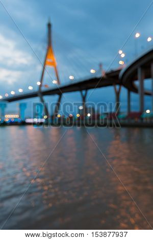 Abstract blurred lights night view, suspension bridge river front, Bangkok Thailand