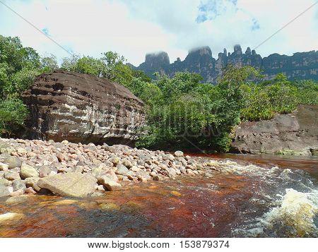 Big rock, huge rock on the bank of river reddish Carrao, among the huge tepuis of Venezuela's Gran Sabana
