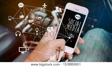Man's hands holding smart phone emitting holographic image of social media related icons inside a car. social media concept