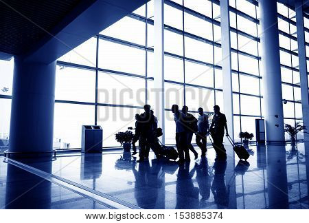 The passengers waiting in the lobby of the airport terminal.
