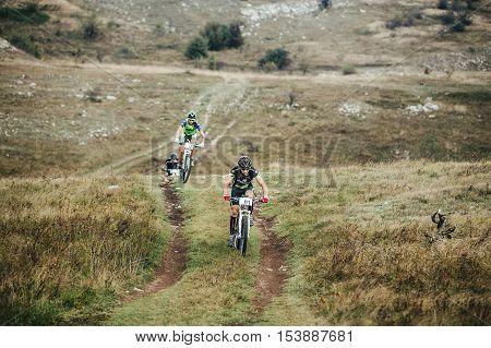 Privetnoye Russia - September 21 2016: three cyclists on mountain bikes rides of uphill during Crimean race mountainbike