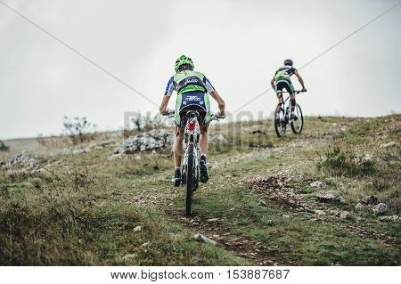 Privetnoye Russia - September 21 2016: two riders cyclist on mountain bikes rise uphill during Crimean race mountainbike