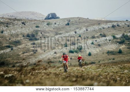 Privetnoye Russia - September 21 2016: two riders rider mountain bike rides on a mountain trail during Crimean race mountainbike