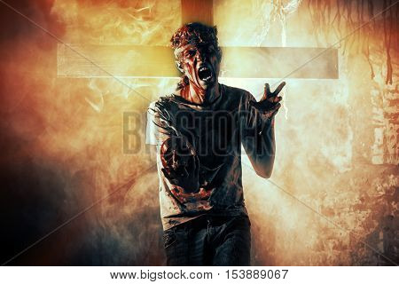 Risen from the dead. Bloody zombie man crawled out of the grave in the cemetery. Halloween.