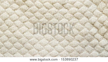 White knitted carpet closeup. Textile texture, off white background. Detailed warm yarn. Knit cashmere, beige wool. Natural woolen fabric, sweater fragment.