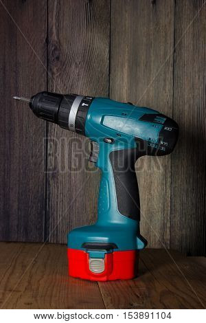 Drill battery on a wooden background with battery