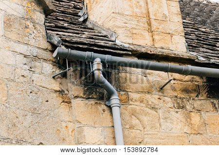 Detail of an old gutter and downspout in a stone wall.