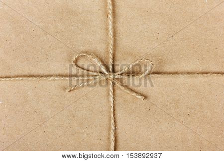 String or twine tied in a bow on kraft paper background. Holiday present or gift concept.