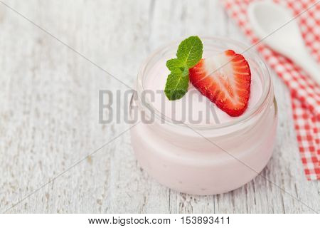 Homemade strawberry yoghurt decorated mint leaves in glass jar on white rustic table, diet and healthy morning breakfast.