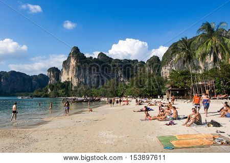 KRABI - JANUARY 20, 2015 : Tourist enjoying a beach walk and sunbathing on a sunny day JANUARY 20, 2015 at Railay Beach in Krabi, Thailand. Railay Beach is a small peninsula with white sand beaches, soaring limestone cliffs, viewpoints, caves and a lagoon