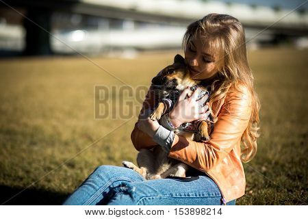 Beautiful Young Blond Woman Walks Her Dog In The Park