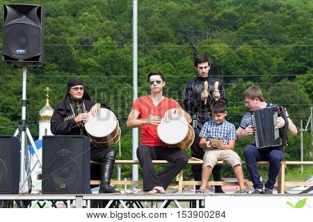 ADYGEA RUSSIA - JULY 25 2015: Adyghe music ensemble of Circassian national costumes playing the scene on the background of green forest ethnic festival in the mountains of Adygea