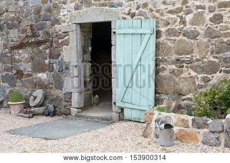 Rustic old stone barn with an open wooden door in Brittany France