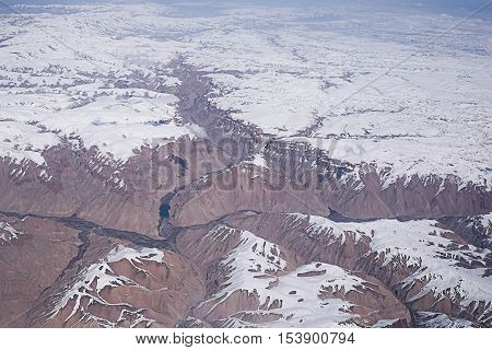 Snowmelt Winter Mountain Landscape, view from the airplane window poster