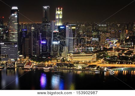 Singapore Singapore - October 2 2016: Night view of the Marina Bay skyline from the Marina of Singapore at night . People are on the promenade that is full of restaurant and shops.