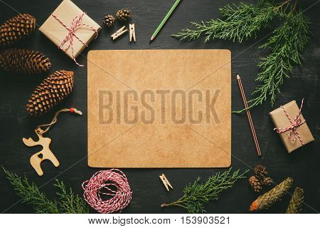 Christmas or New Year background dark moody board with a space for greeting text decorated with various seasonal holiday decorative elements such as fir branches cones and gift boxes flat lay view from above